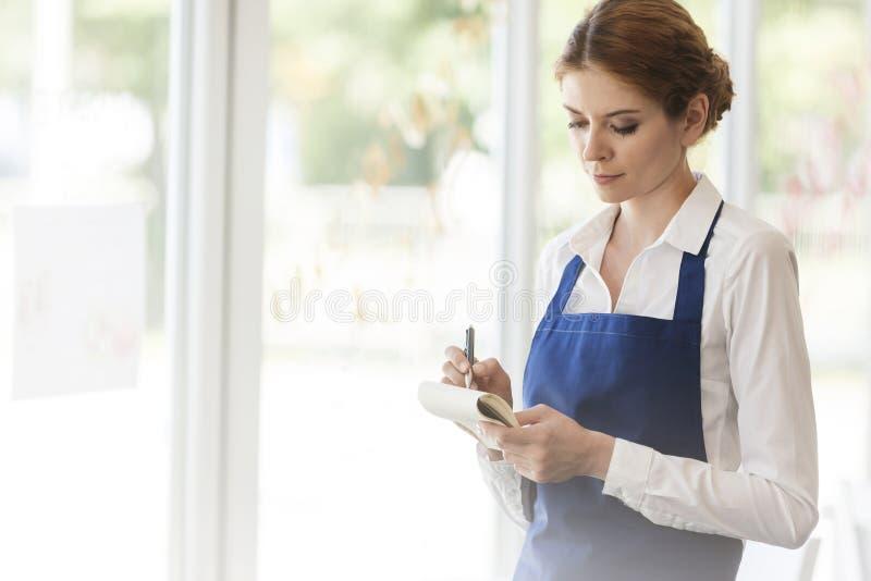 Piękna młoda kelnerka pisze na notepad przy restauracją fotografia stock