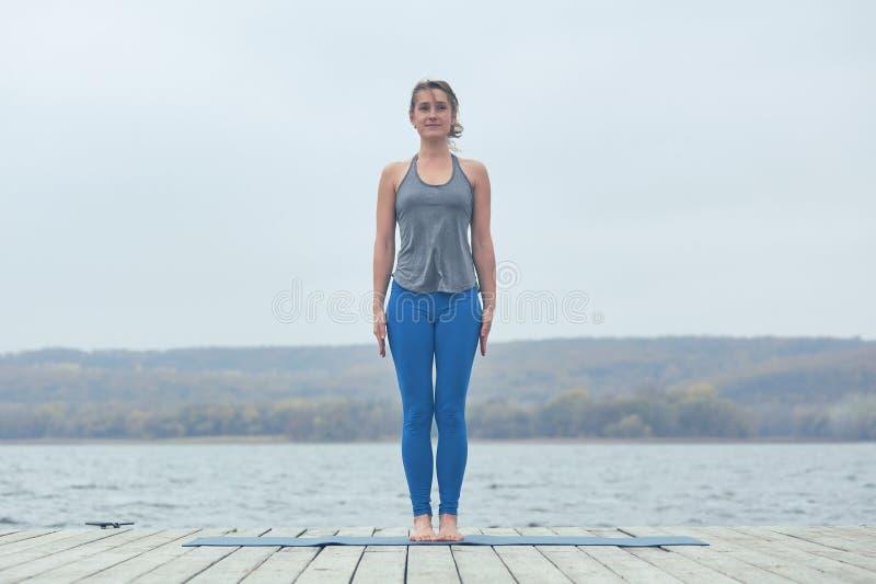 Piękna młoda kobieta ćwiczy joga asana Tadasana - Halna poza na drewnianym pokładzie blisko jeziora zdjęcia royalty free