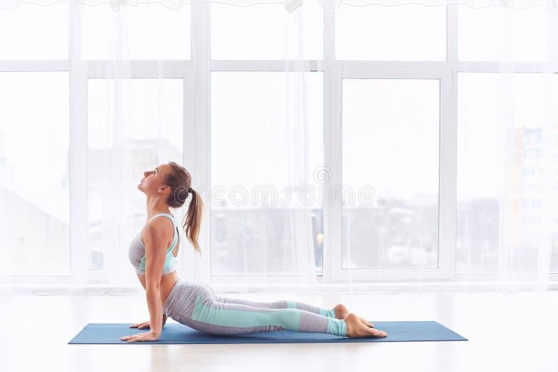 Piękna młoda kobieta ćwiczy joga asana Urdhva Mukha Svanasana - oddolny obszycie pies przy joga klasą obraz royalty free