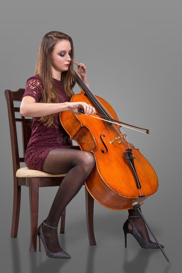 Piękna młoda kobieta bawić się wiolonczelę Odizolowywający na popielatym tle zdjęcia royalty free