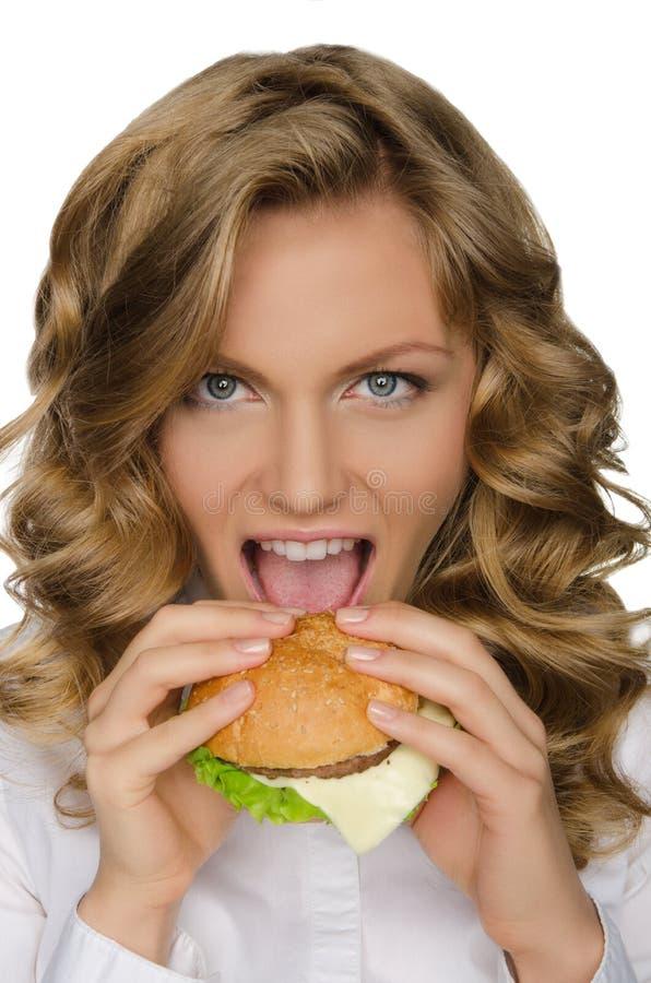 Piękna młoda kobieta bierze kąsek hamburger fotografia stock