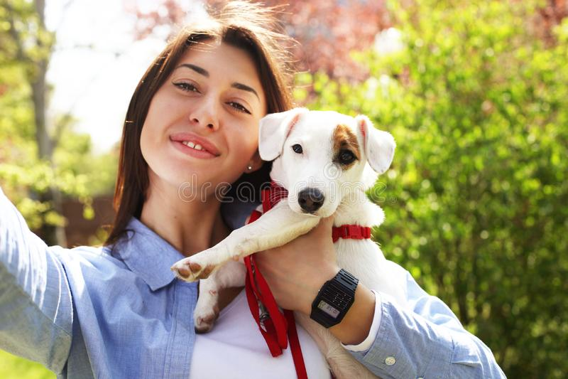 Piękna młoda kobieta bierze selfie z jej ślicznym dźwigarki Russell teriera szczeniakiem na pinkinie w parku, zielonej trawie & u zdjęcie royalty free