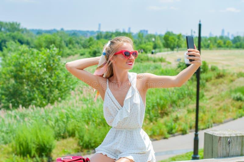 Piękna młoda kobieta bierze selfie z jej smartphone w parku fotografia stock