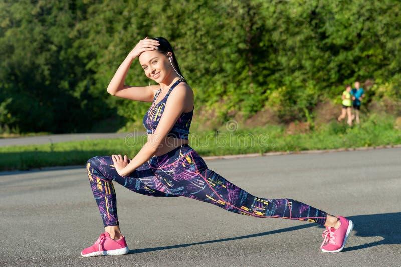 Piękna młoda kobieta, brunetka, robi rozgrzewce przed jogging w parku, będący ubranym hełmofon, słucha muzyka obraz stock
