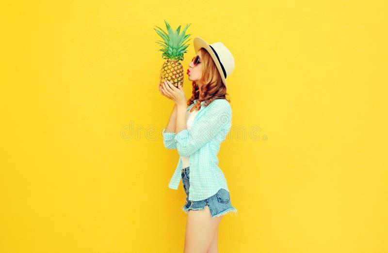 Piękna młoda kobieta całuje tropikalnego ananasa w lato słomianym kapeluszu, skróty na kolorowym kolorze żółtym obrazy stock