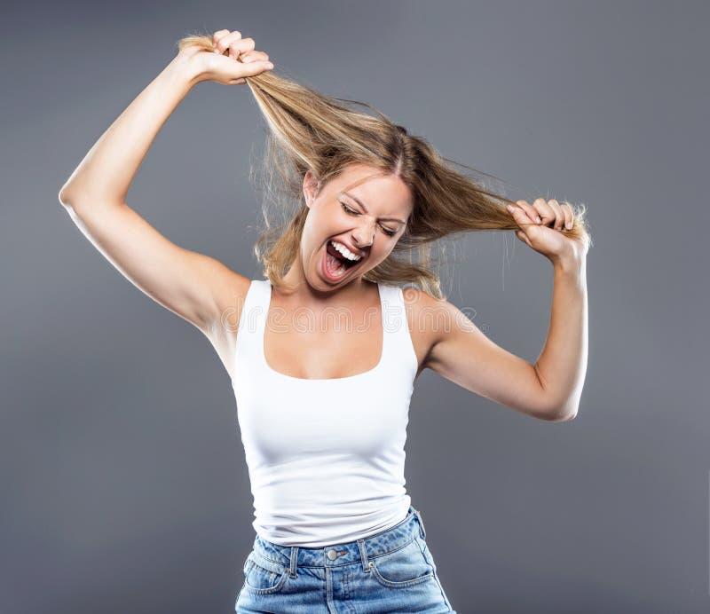 Piękna młoda kobieta ciągnie jej włosy nad szarym tłem zdjęcie royalty free