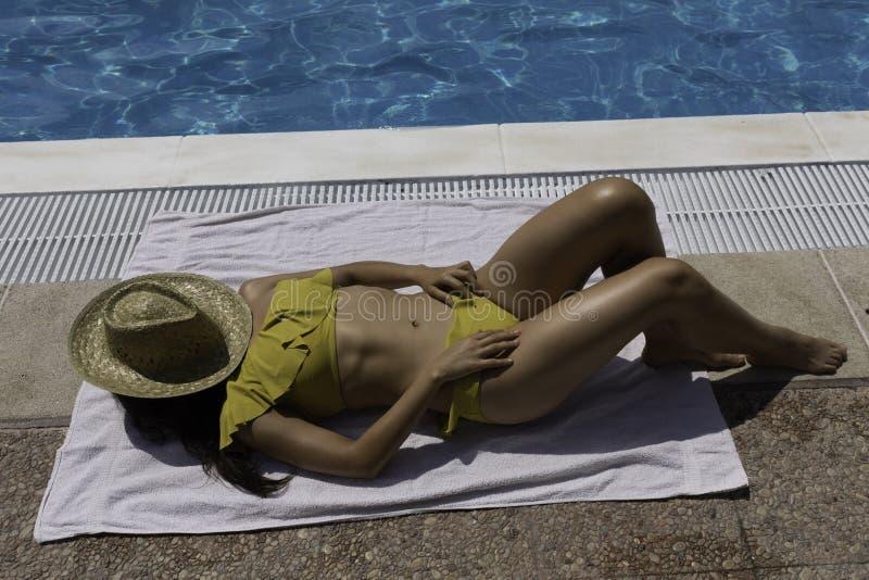 Piękna młoda kobieta cieszy się słońce przy krawędzią basen zdjęcie stock