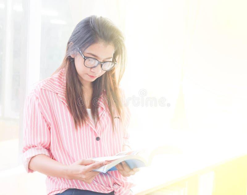 Piękna młoda kobieta czyta książkę znajdować out informację w bibliotece Ludzie, wiedza, edukacja i szkoły pojęcie, obraz royalty free