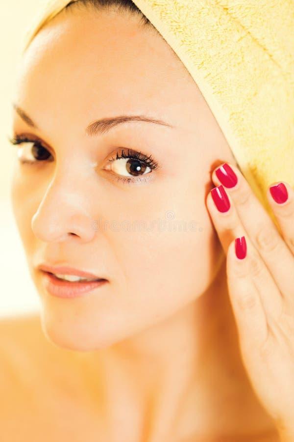 Piękna młoda kobieta delikatnie dotyka jej twarz zdjęcie stock