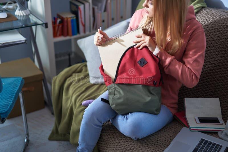 Piękna młoda kobieta dostaje sketchbook od plecaka obraz royalty free