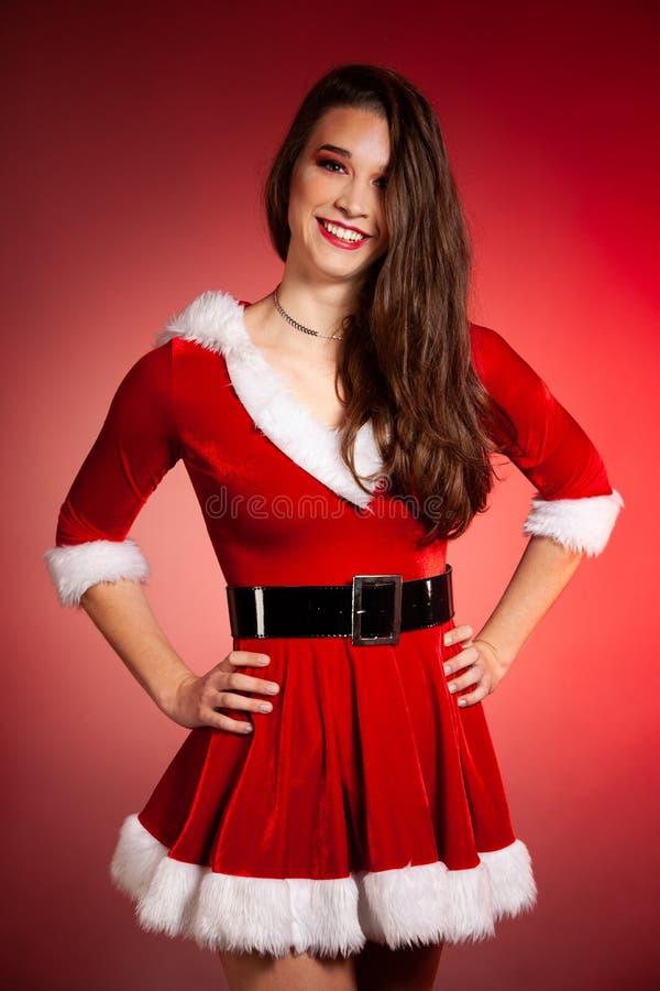 Piękna młoda kobieta dostarcza teraźniejszość nad czerwonym tłem w Santa sukni dla bożych narodzeń obraz royalty free