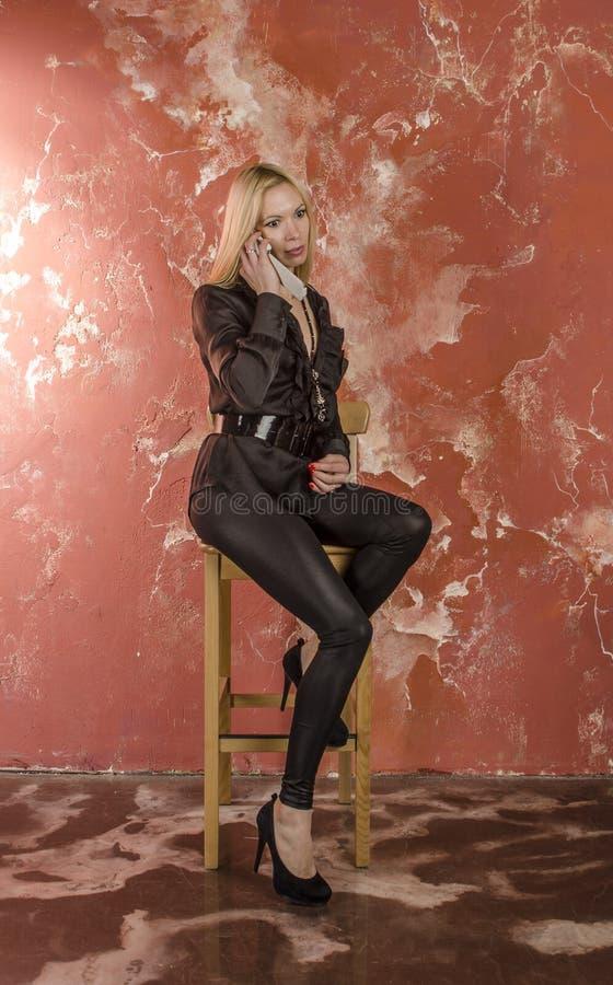 Piękna młoda kobieta Emocjonalnie opowiada na telefonie z torbą moda w czarnej koszula i fotografia royalty free