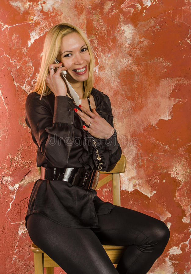 Piękna młoda kobieta Emocjonalnie opowiada na telefonie z torbą moda w czarnej koszula i fotografia stock
