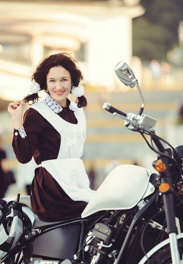 Piękna młoda kobieta, fryzura i łęki, outdoors z motocyklem Szczęśliwy i zdrowy ubierający w Radzieckim mundurku szkolnym dziewcz obraz royalty free