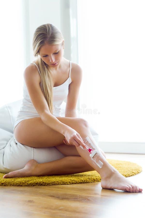Piękna młoda kobieta goli jej atracctive nogi obraz stock