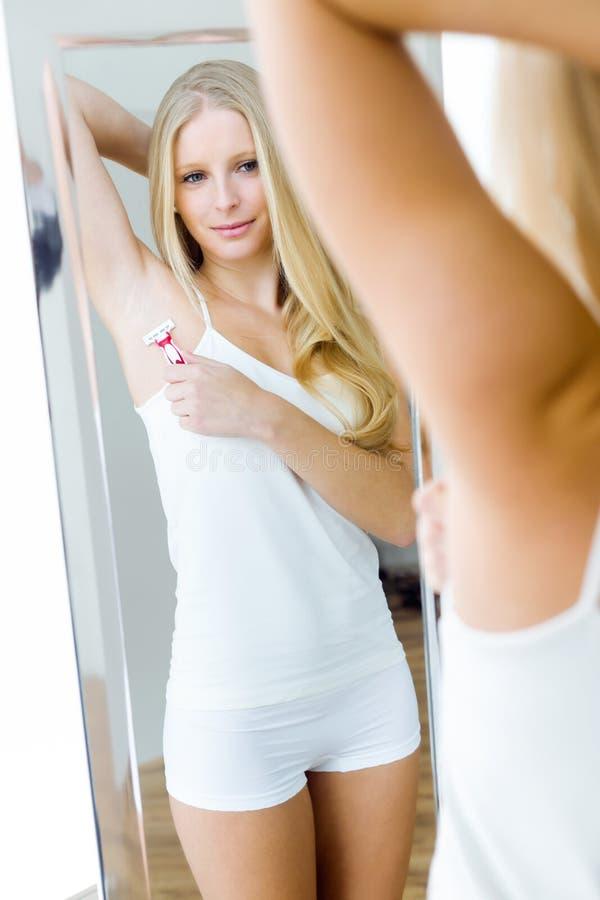 Piękna młoda kobieta goli jej pachę w bieliźnie obraz royalty free