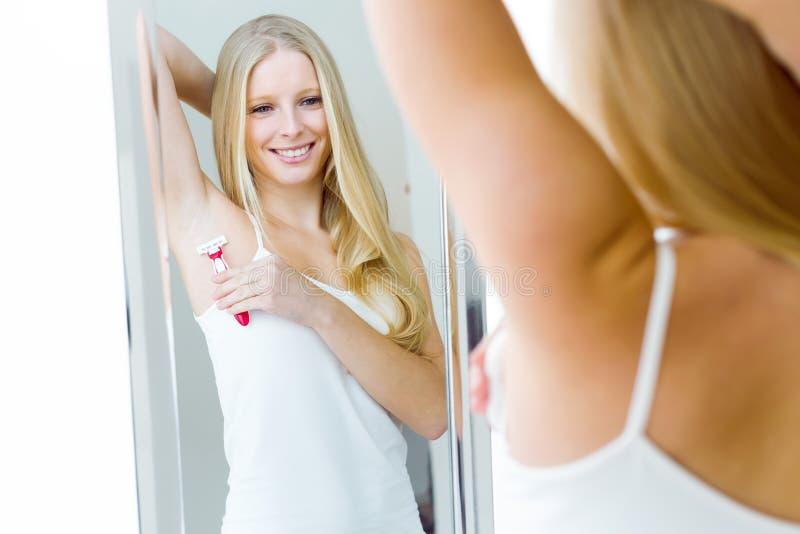 Piękna młoda kobieta goli jej pachę w bieliźnie zdjęcie royalty free