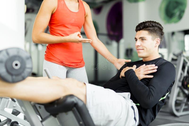 Piękna młoda kobieta instruuje młodego człowieka w gym zdjęcie royalty free