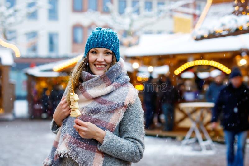 Piękna młoda kobieta je biała czekolada zakrywać owoc na skewer na tradycyjnych Niemieckich bożych narodzeniach wprowadzać na ryn obraz stock