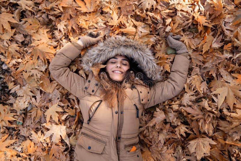 Piękna młoda kobieta jest łgarskim puszkiem na liściach, cieszy się jesień zdjęcia stock