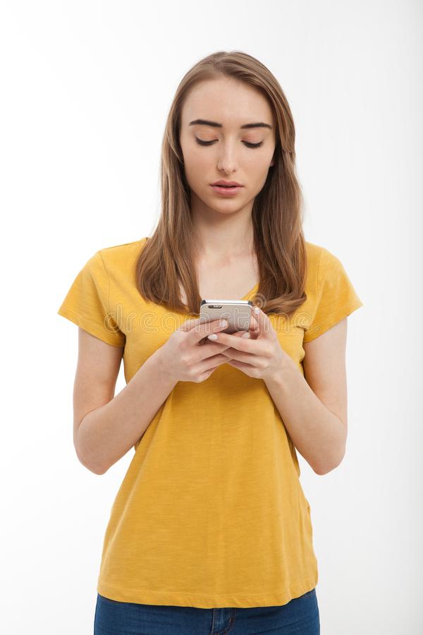 Piękna młoda kobieta jest ubranym żółtą t koszula i texting na smartphone odizolowywającym na bielu Odbitkowa przestrzeń up i egz zdjęcie stock