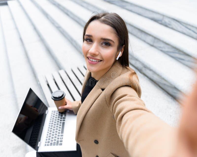 Piękna młoda kobieta jest ubranym jesień żakiet używać laptop obrazy stock