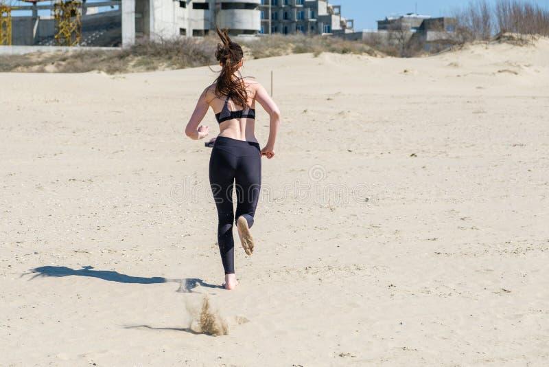 Piękna młoda kobieta Jogging na plaży, tylni widok obrazy royalty free