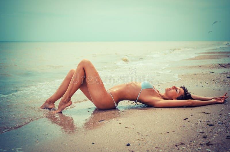 Piękna młoda kobieta kłaść w dennym wybrzeżu z tonowaniem - obraz royalty free