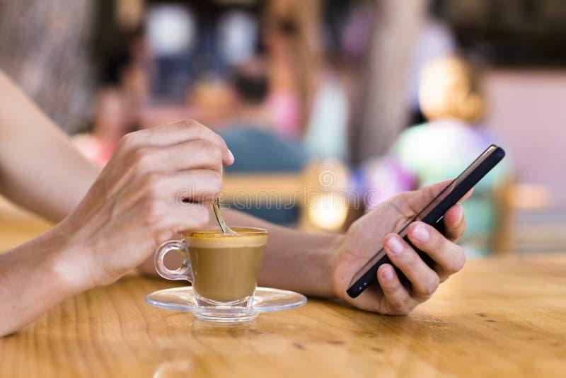 piękna młoda kobieta ma filiżanka kawy w tarasie i używa telefon komórkowego outdoors Lato, wakacje i styl życia, obrazy royalty free