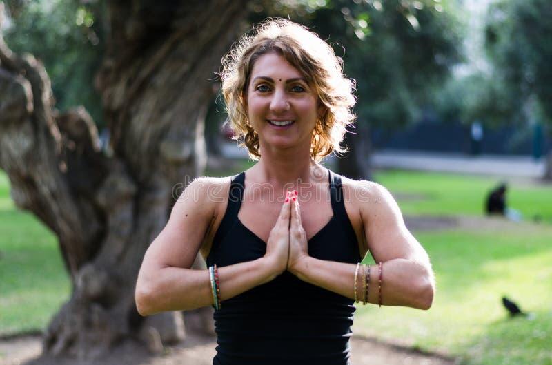 Piękna młoda kobieta medytuje w joga asana Padmasana - Lotosowa poza na drewnianym pokładzie w jesień parku zdjęcie royalty free
