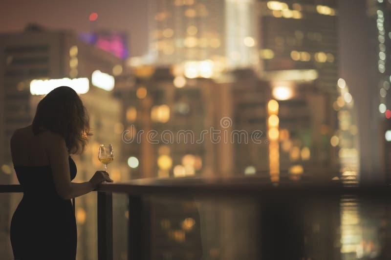 Piękna młoda kobieta na balkonie w czarnej sukni z szkłem wino na tle nocy miasto zdjęcie stock