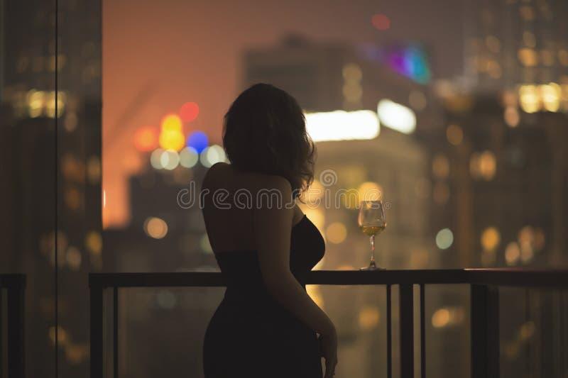 Piękna młoda kobieta na balkonie w czarnej sukni z szkłem wino na tle nocy miasto zdjęcia royalty free