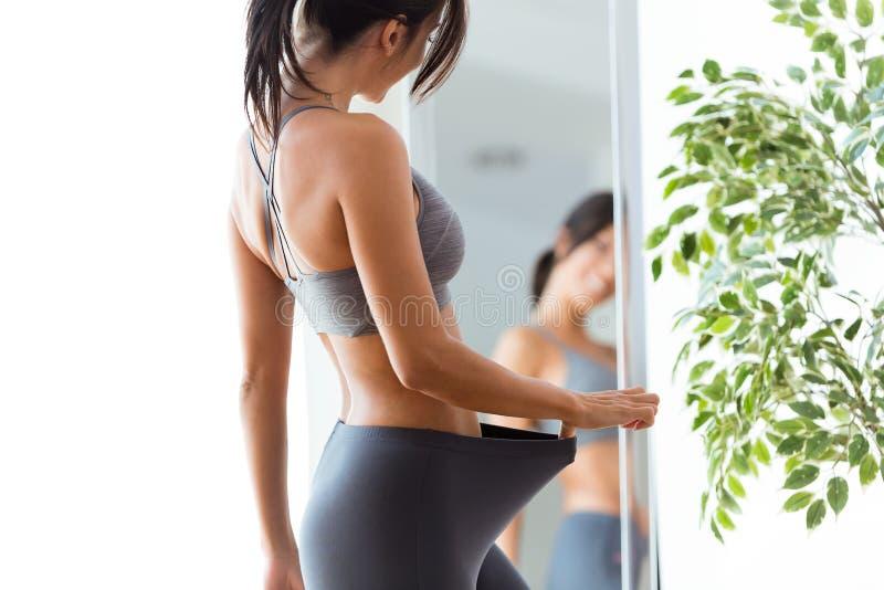 Piękna młoda kobieta ono patrzeje w domu odbicie w lustrze obrazy stock