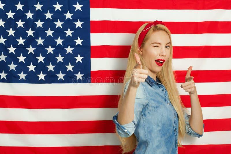Piękna młoda kobieta ono uśmiecha się i gestykuluje przeciw tłu flaga amerykańska na dniu niepodległości zdjęcia stock