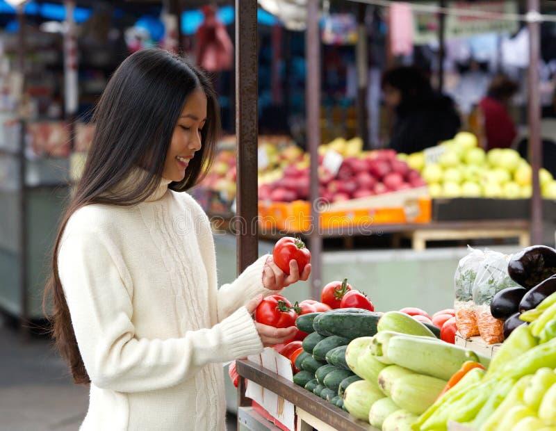 Piękna młoda kobieta ono uśmiecha się przy jarzynowym rynkiem zdjęcie stock