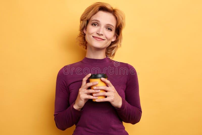 Piękna młoda kobieta ono uśmiecha się, trzymający takeaway kawę obraz stock