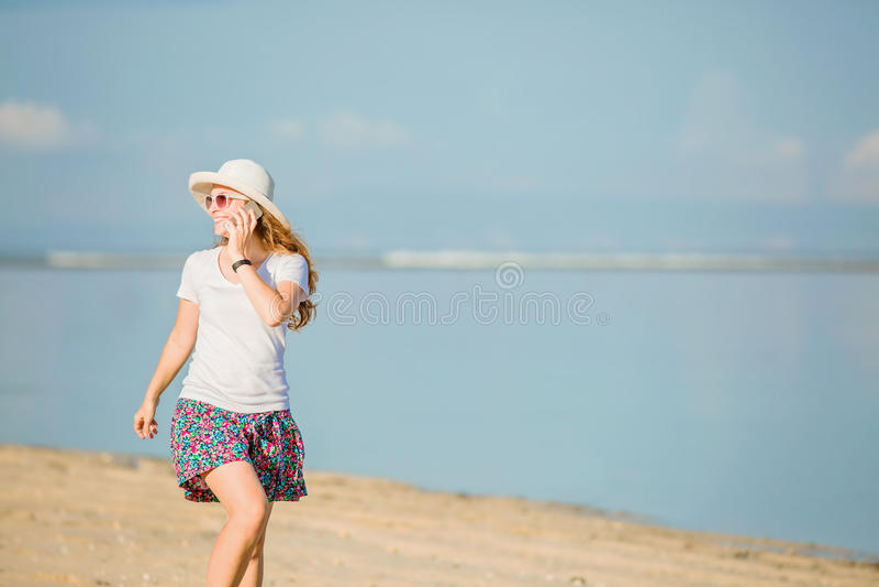 Download Piękna Młoda Kobieta Opowiada Dalej Przy Plażą Obraz Stock - Obraz złożonej z suknia, pokój: 57657031