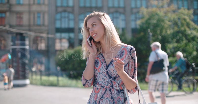 Piękna młoda kobieta opowiada na telefonie podczas słonecznego dnia obrazy royalty free