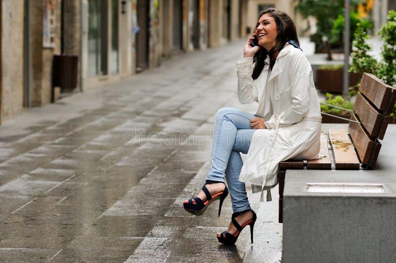 Piękna młoda kobieta opowiada na telefonie w miastowym tle fotografia royalty free