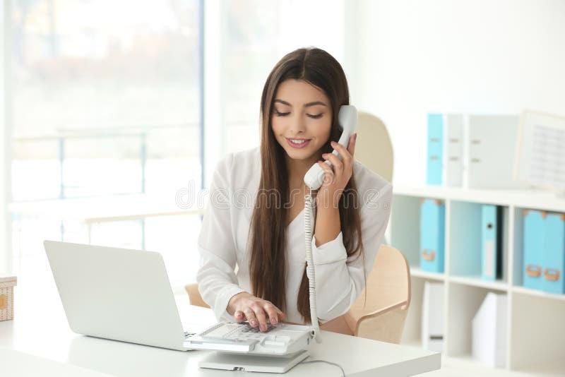 Piękna młoda kobieta opowiada telefonem podczas gdy pracujący w biurze fotografia stock