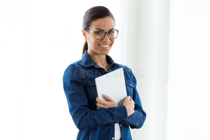 Piękna młoda kobieta patrzeje kamerę z eyeglasses podczas gdy trzymający cyfrową pastylkę nad białym tłem obrazy royalty free