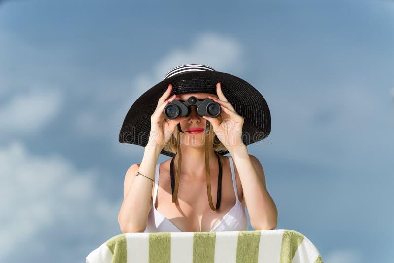 Piękna młoda kobieta patrzeje przez lornetek przy th w bikini fotografia stock