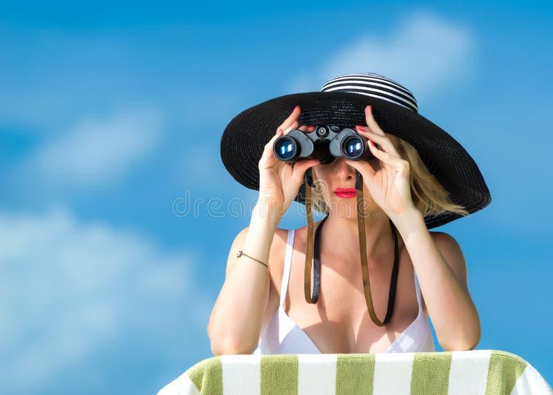 Piękna młoda kobieta patrzeje przez lornetek przy tropikalną plażą w bikini obrazy stock
