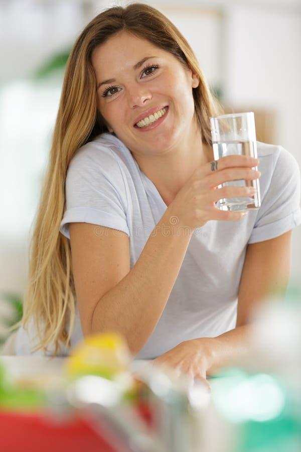 Piękna młoda kobieta pijąca wodę w szklanej szklance w domu zdjęcie stock