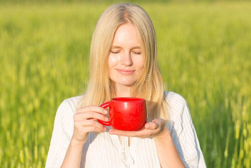 Piękna młoda kobieta pije herbaty, kawy/outdoors tła pola zieleni lato zdjęcie stock