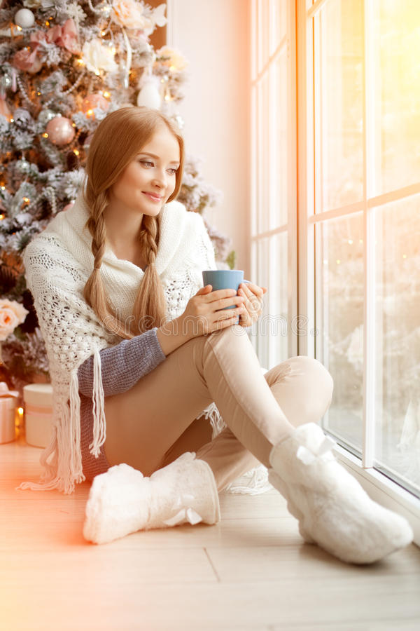 Piękna młoda kobieta pije herbaty przy choinką Beauti obrazy royalty free