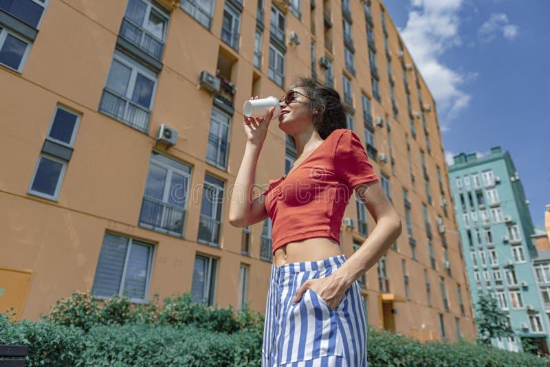 Piękna młoda kobieta pije kawę na ulicie zdjęcia royalty free