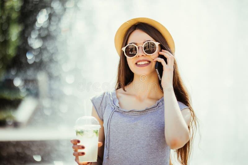 Piękna młoda kobieta pije mojito wyśmienicie odświeżającego koktajl na słonecznym dniu w ulicie i opowiada telefon Owocowi napoje zdjęcie stock