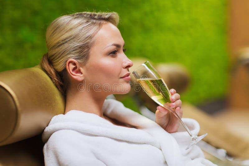 Piękna młoda kobieta pije szampana przy zdrojem zdjęcie royalty free