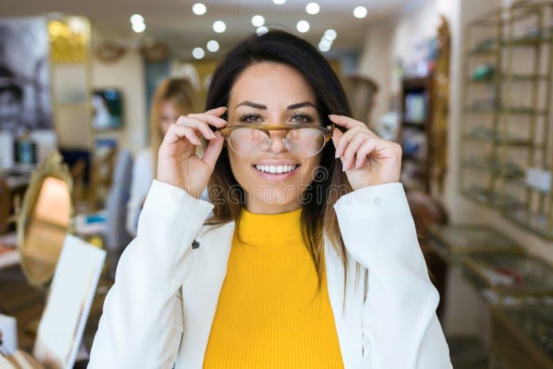 Piękna młoda kobieta pokazuje ona nowych eyeglasses w wzrokowym sklepie podczas gdy patrzejący kamerę zdjęcia stock